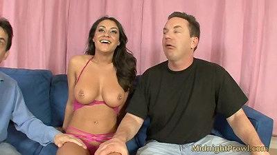 Bombshell Charlie Chase sitting with her tits out of her bra and fingered by two men